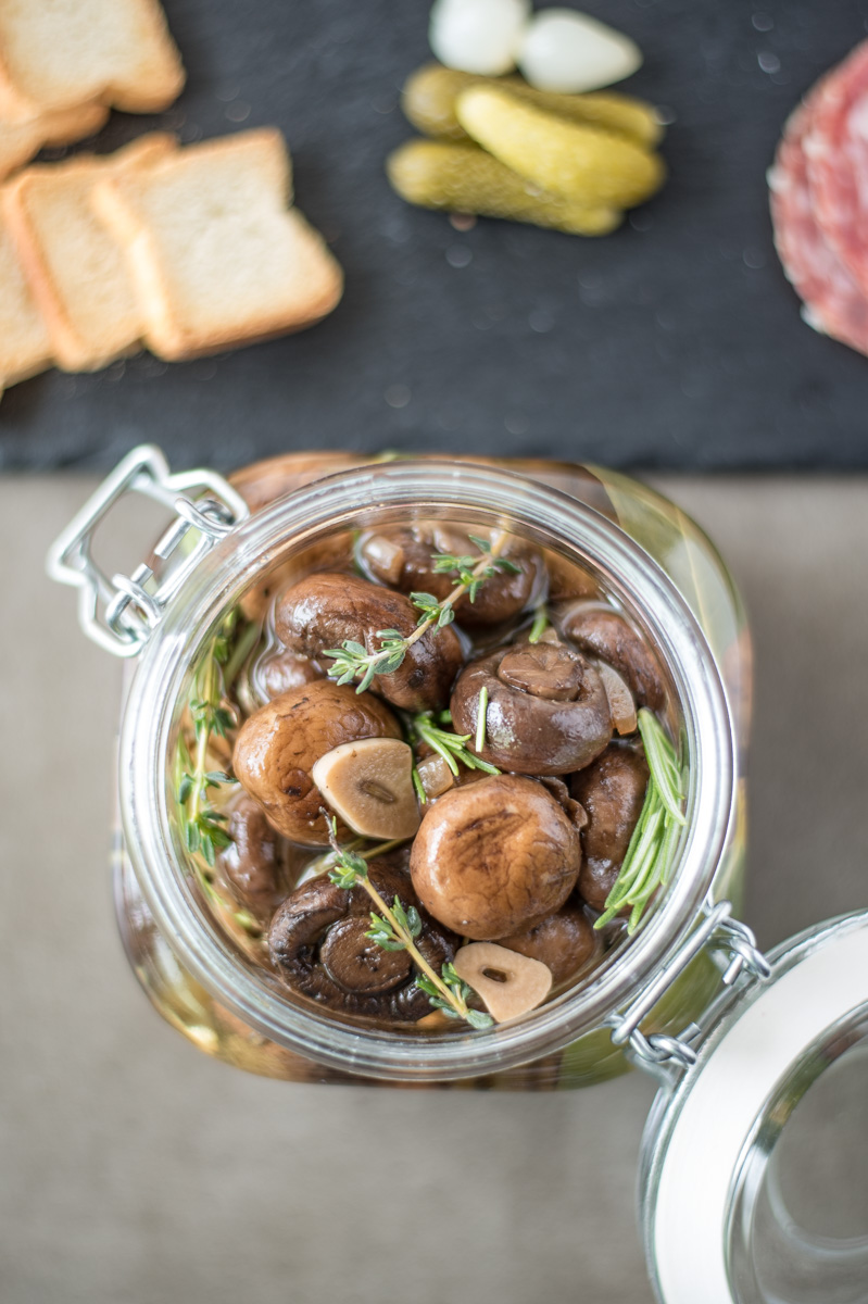 Herb and garlic marinated mushrooms bring something different to a charcuterie board. Mushrooms are cooked with thyme, rosemary, garlic and lemon, then jarred and allowed to marinate to intensify the flavors.