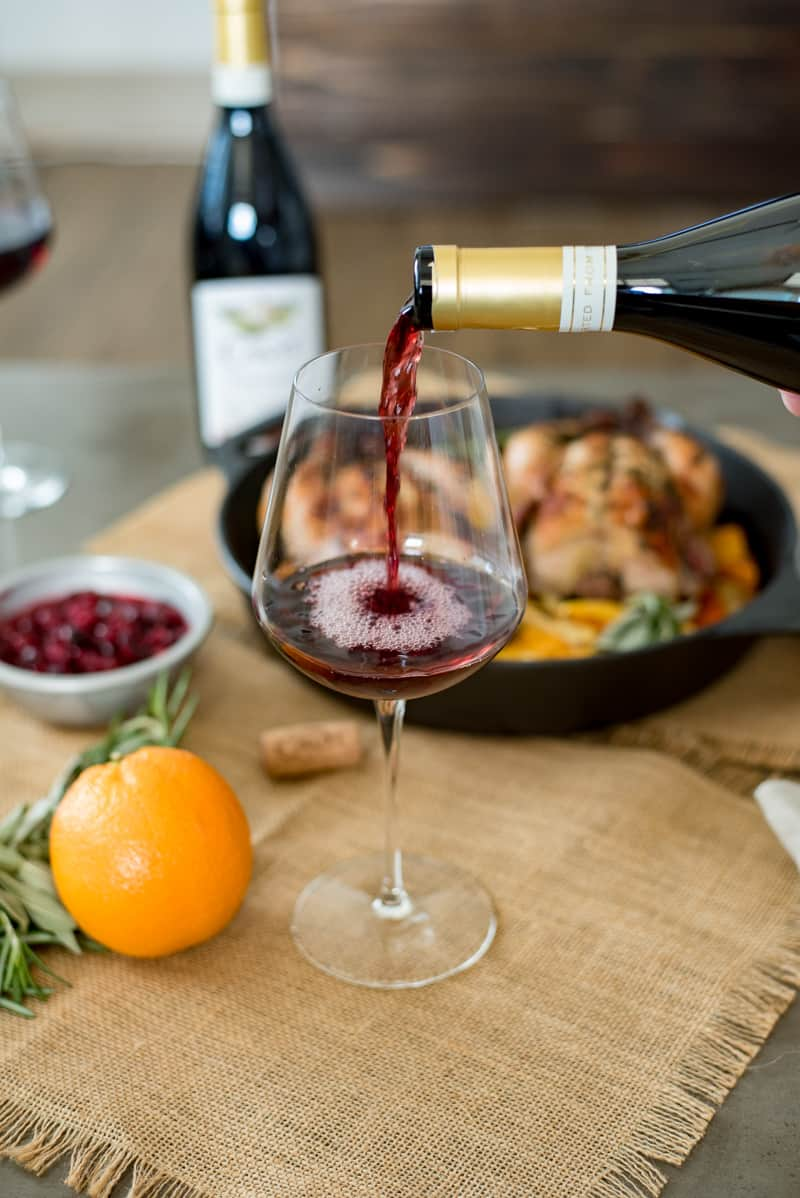 Pouring a glass of Pinot Noir to pair with the Cornish hens