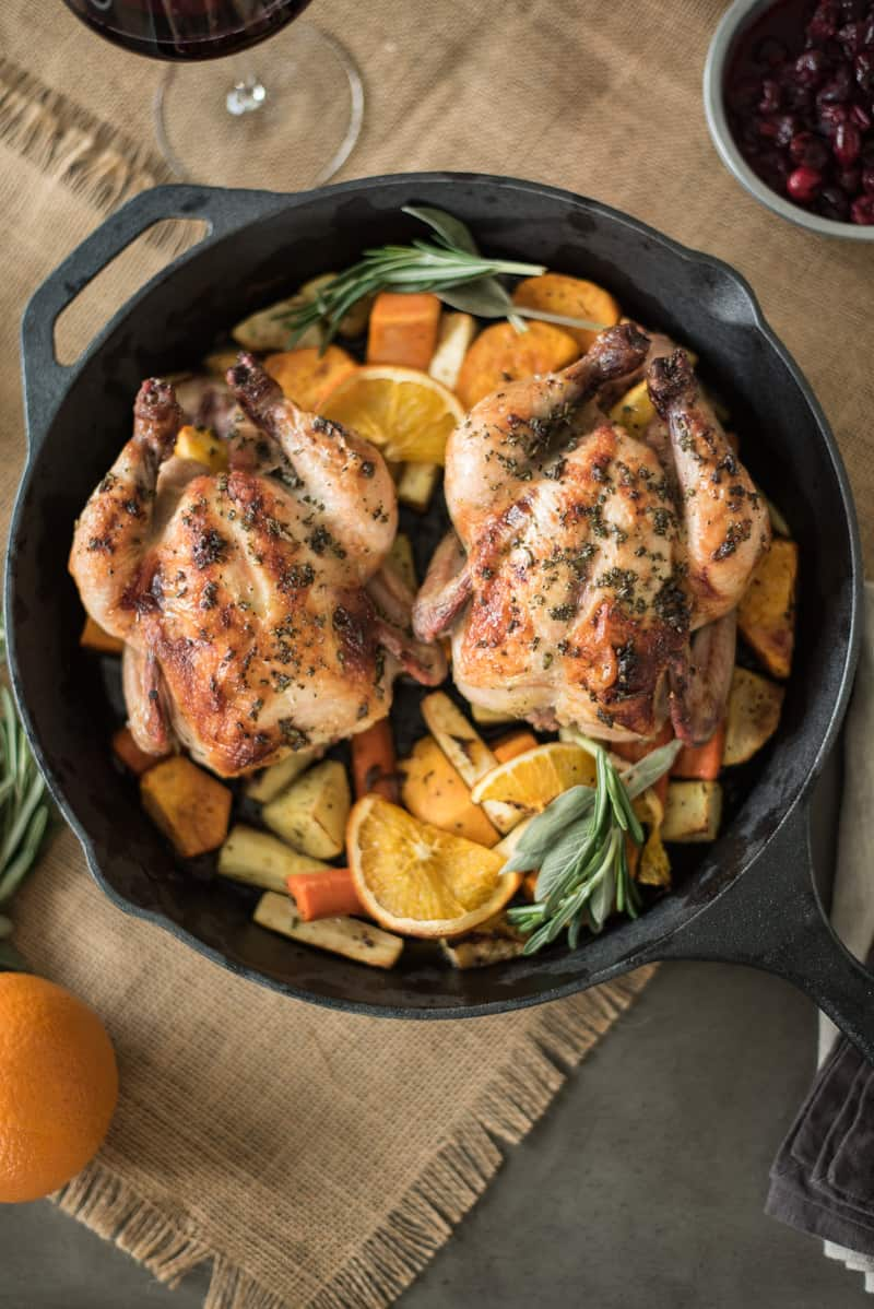 Herb roasted Cornish hens with root vegetables cooked in a cast iron skillet with fresh orange and root vegetables