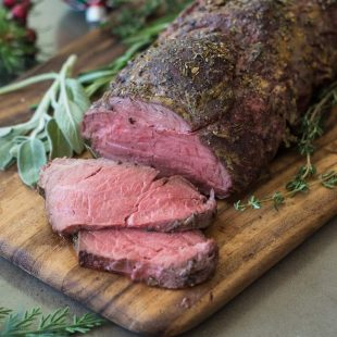 A sliced beef tenderloin coated with herbs