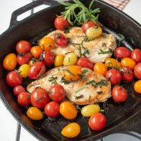A cast iron skillet with 2 chicken breast, tomatoes and herbed butter
