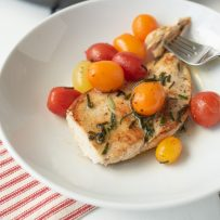 A chicken breast with herbed brown butter and tomatoes on a white plate