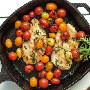 Herbed Brown Butter Chicken with Tomatoes in a cast iron skillet garnished with fresh rosemary