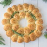 Holiday rosemary bread wreath is a stunning holiday recipe that can be used as an edible centerpiece. Soft bread rolls flavored with fresh rosemary and parmesan.