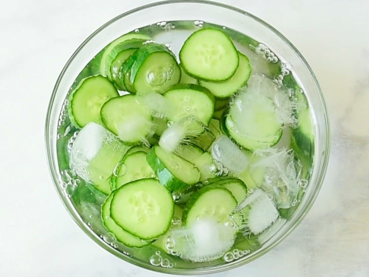 Cucumber slices in a bowl of ice water