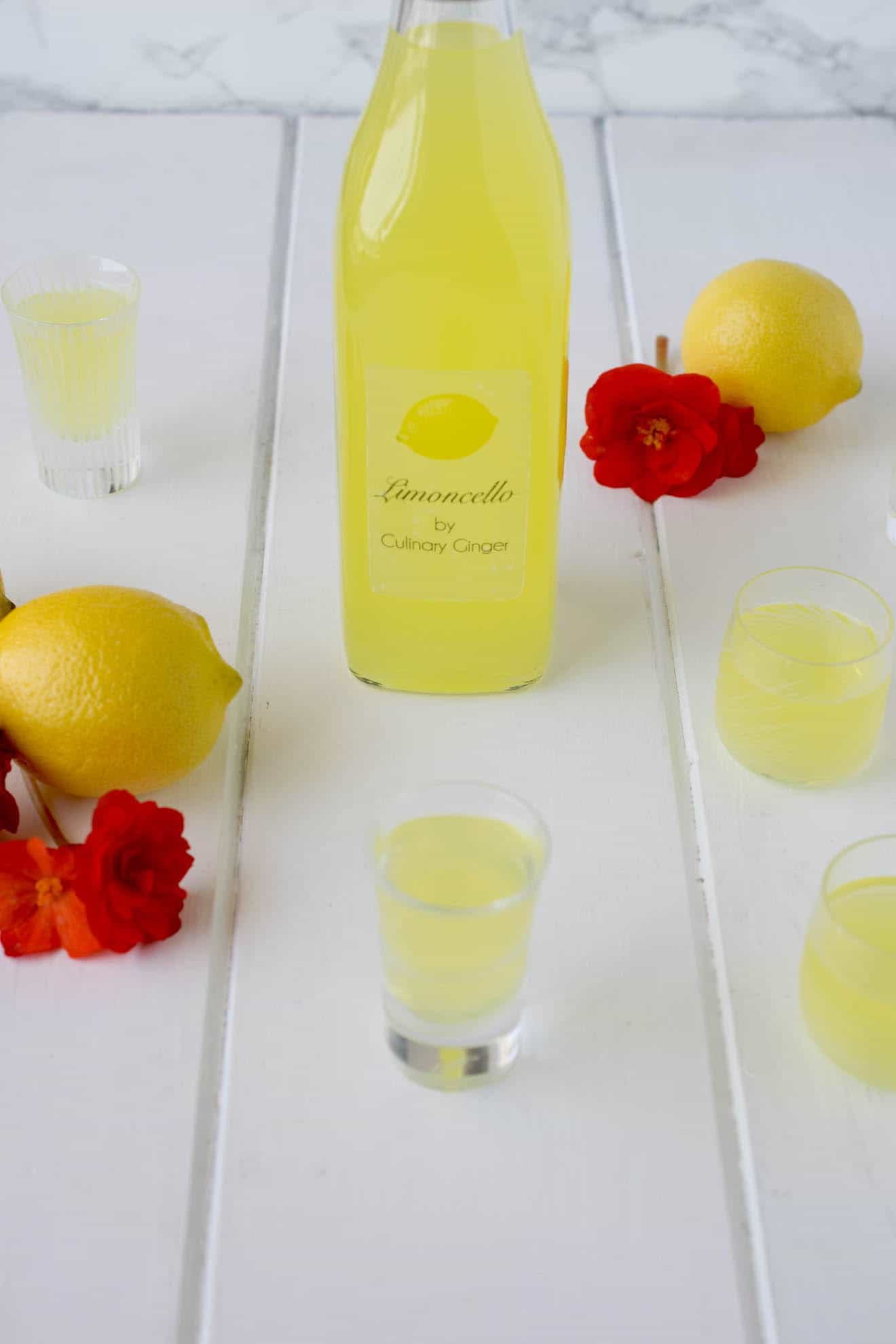 A bottle of limoncello with glasses, lemons and red flowers