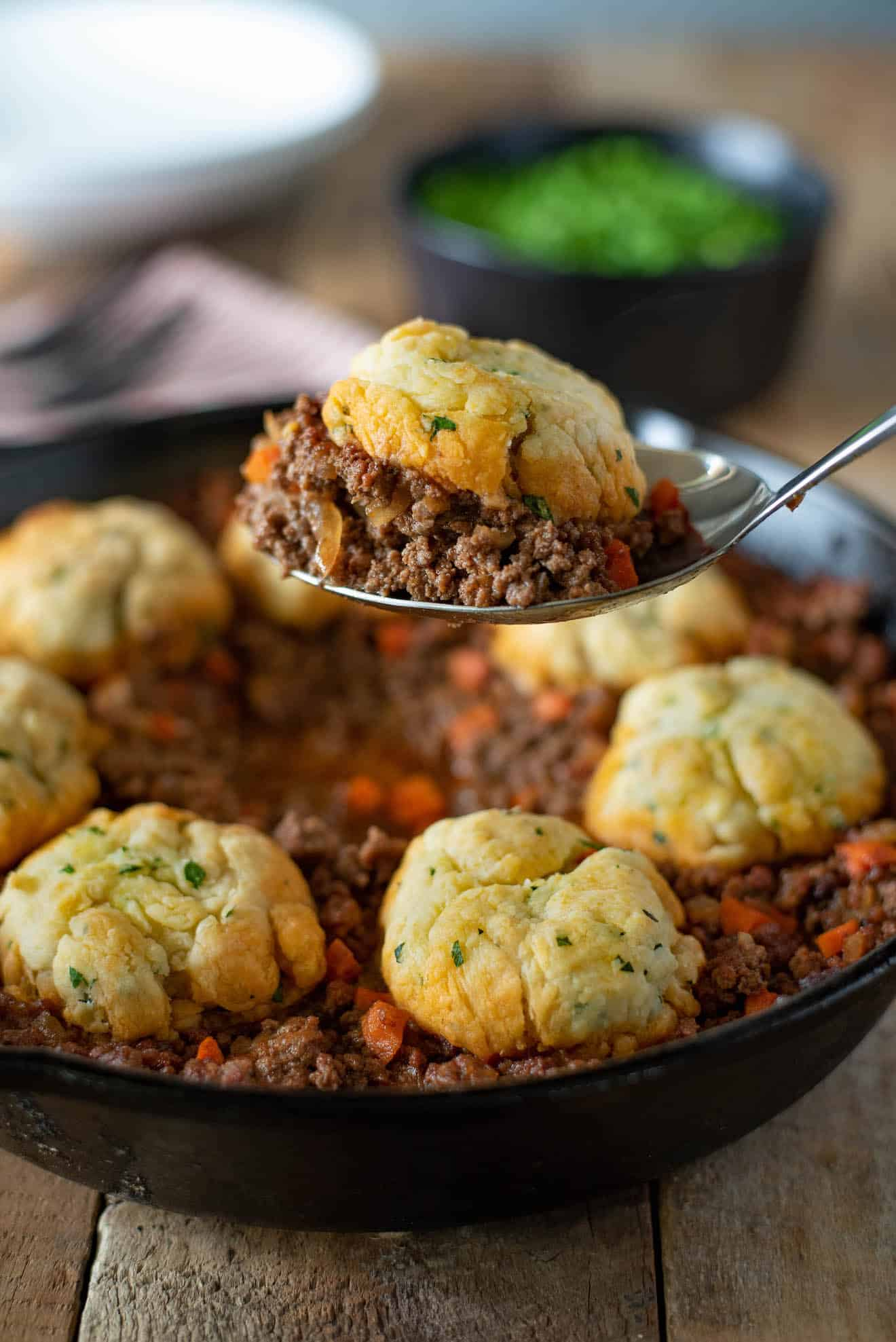 A spoon full of minced beef and dumplings