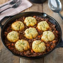 A cast iron skillet with minced beef and dumplings