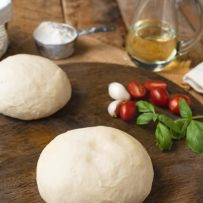Yeast free pizza dough on a pizza board with tomatoes, basil, garlic and oil