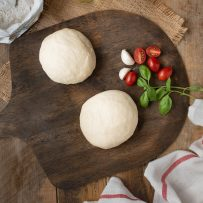 2 pizza dough balls on a board with tomatoes and basil