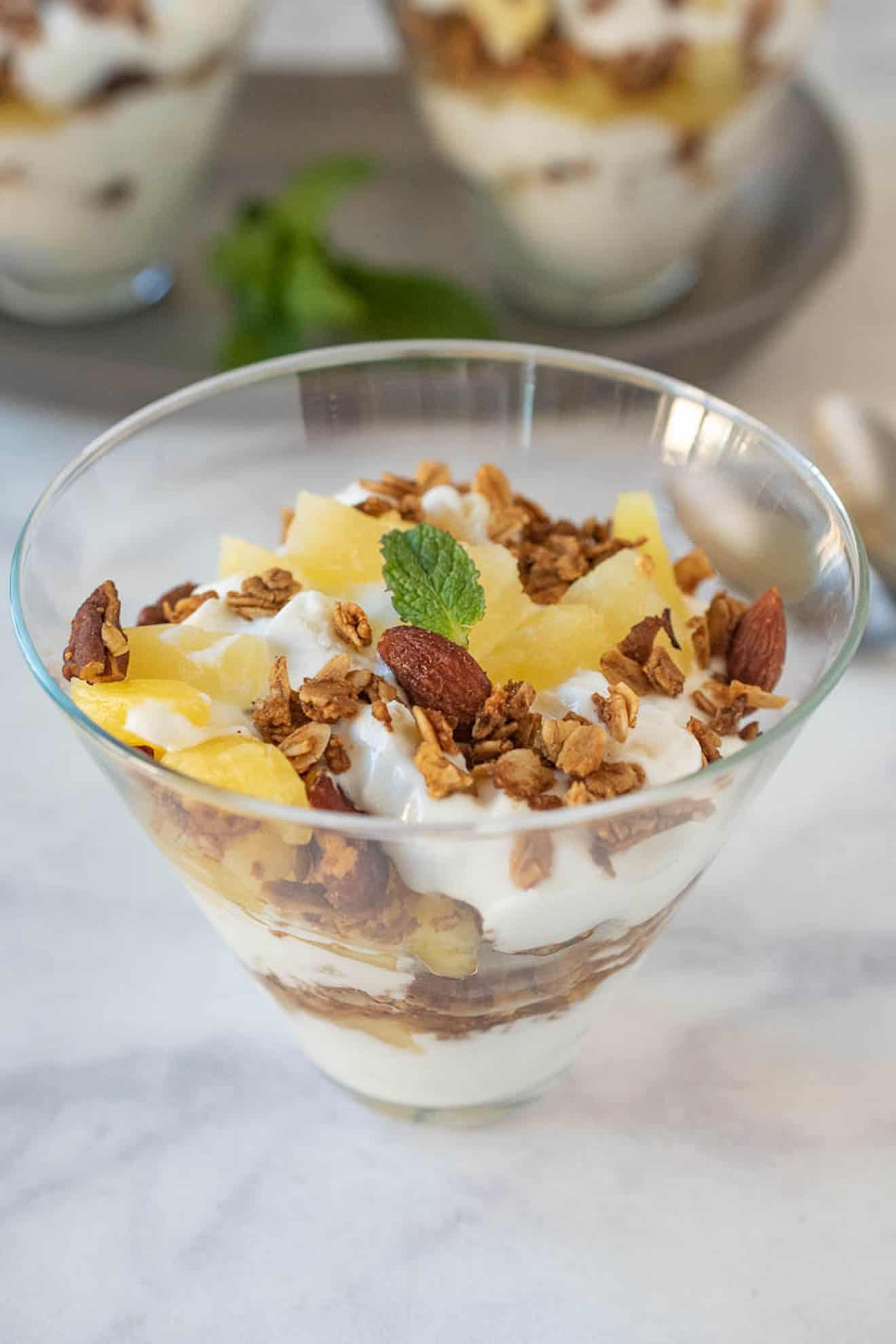 A glass bowl with yogurt, fresh pineapple and granola