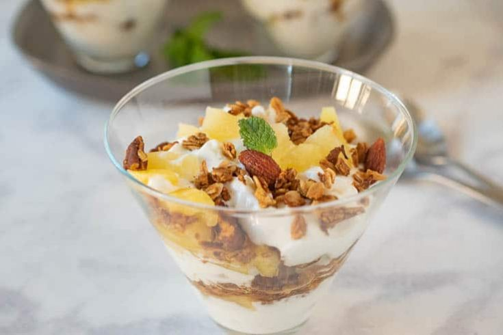 Layers of yogurt with granola and pineapple in a glass bowl