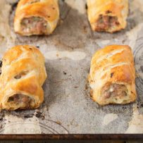 4 sausage rolls on a baking sheet fresh out of the oven