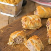 A sausage roll cut open showing the sausage filling and flaky pastry
