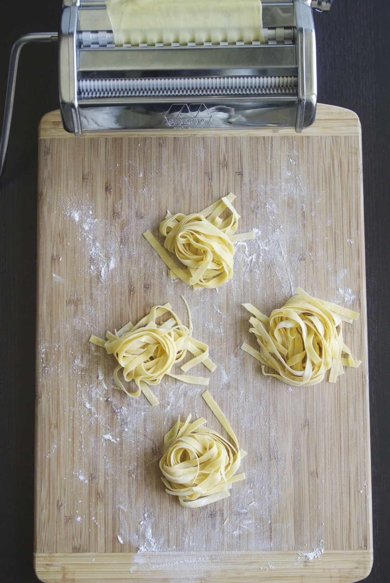 A pasta machine and homemade tagliatelle pasta