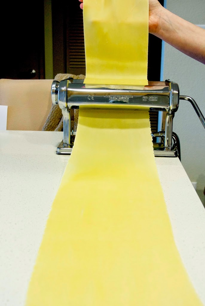 Pasta dough being fed through a pasta maker