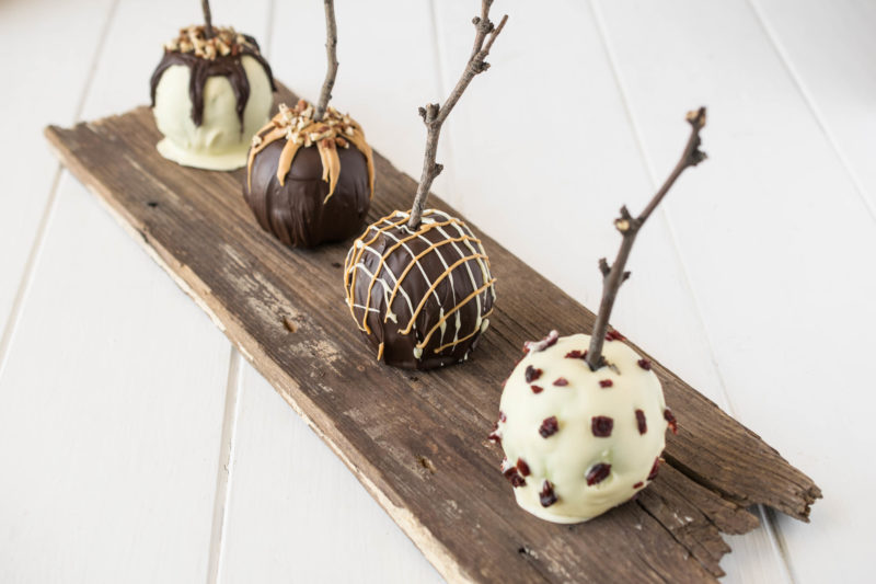 An old plank of wood with the chocolate apples lined up