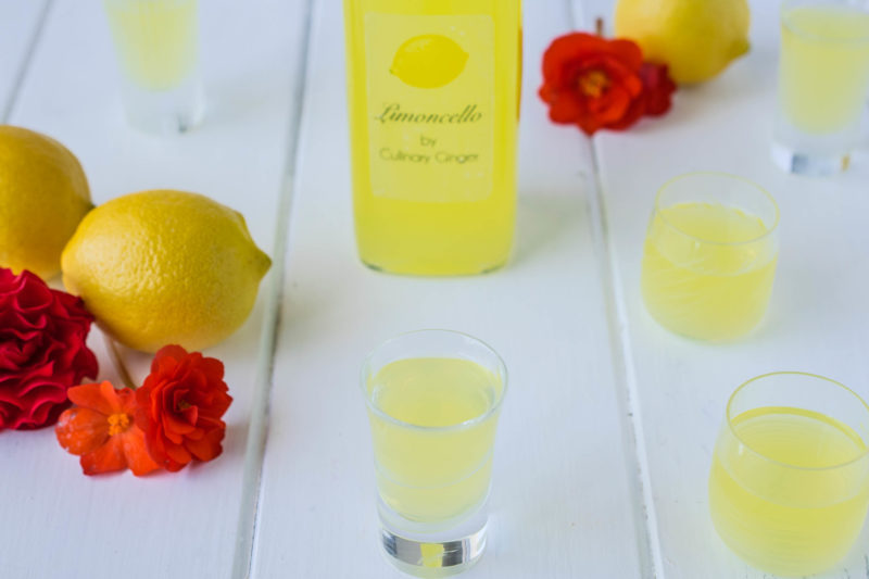 Small shot glasses of limoncello with a lemon and red flowers