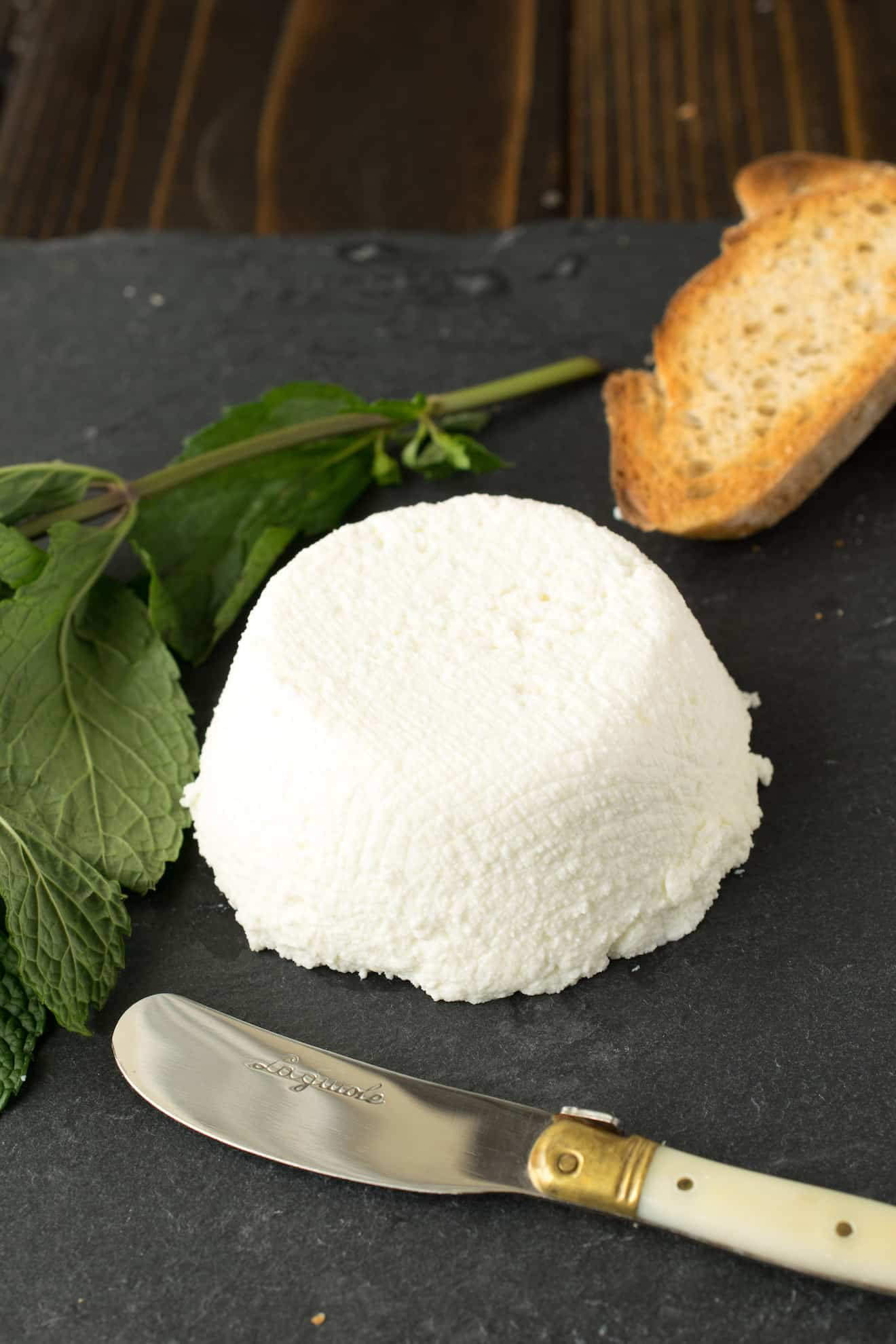 Homemade ricotta with crusty bread and a knife.