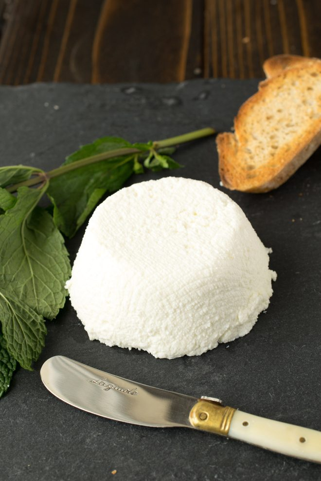 A mound of ricotta with crusty bread and a knife
