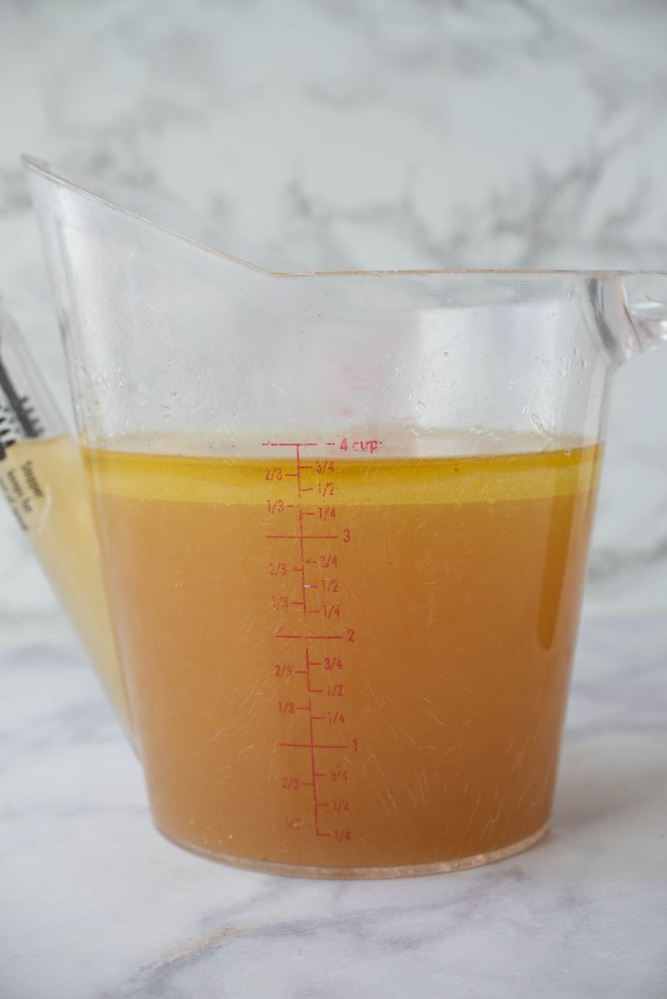 A jug filled with chicken broth
