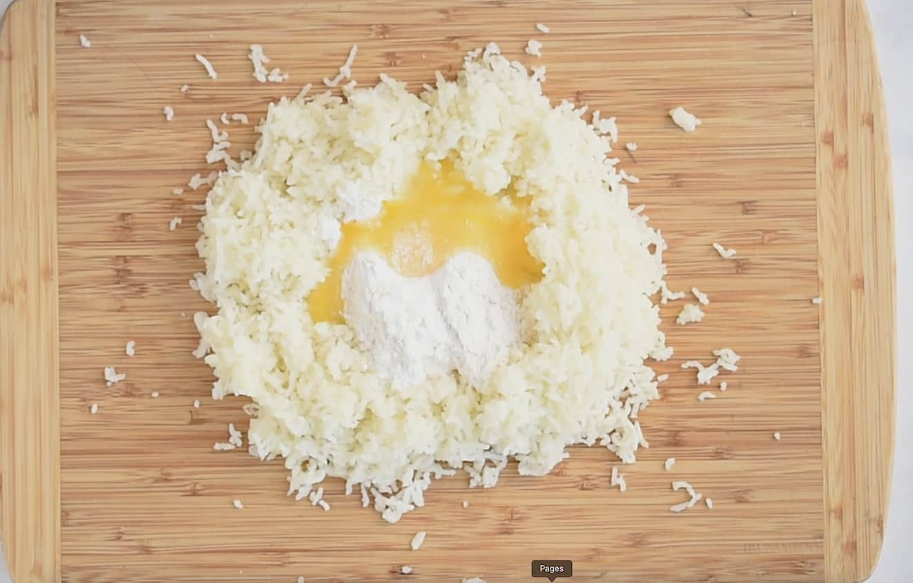 Mashed potato on a board getting mixed with flour and egg