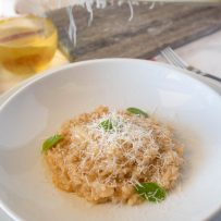 Grating Parmesan cheese onto a plate of risotto with fresh basil leaves