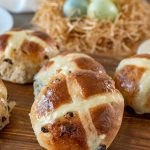 A closeup of a hot cross bun on a board with Easter eggs