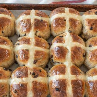 12 hot cross buns on a baking sheet fresh out of the oven
