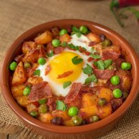 A terracotta bowl filled with potatoes, peas and chorizo in a tomat sauce topped with an egg