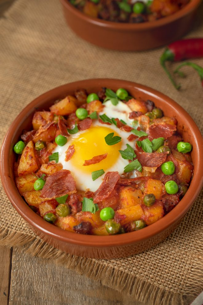 Huevos a la Flamenca (Gypsy Eggs)A terracotta bowl filled with potatoes, peas and chorizo in a tomat sauce topped with an egg