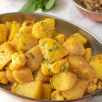 An oval serving dish full of Indian aloo gobi