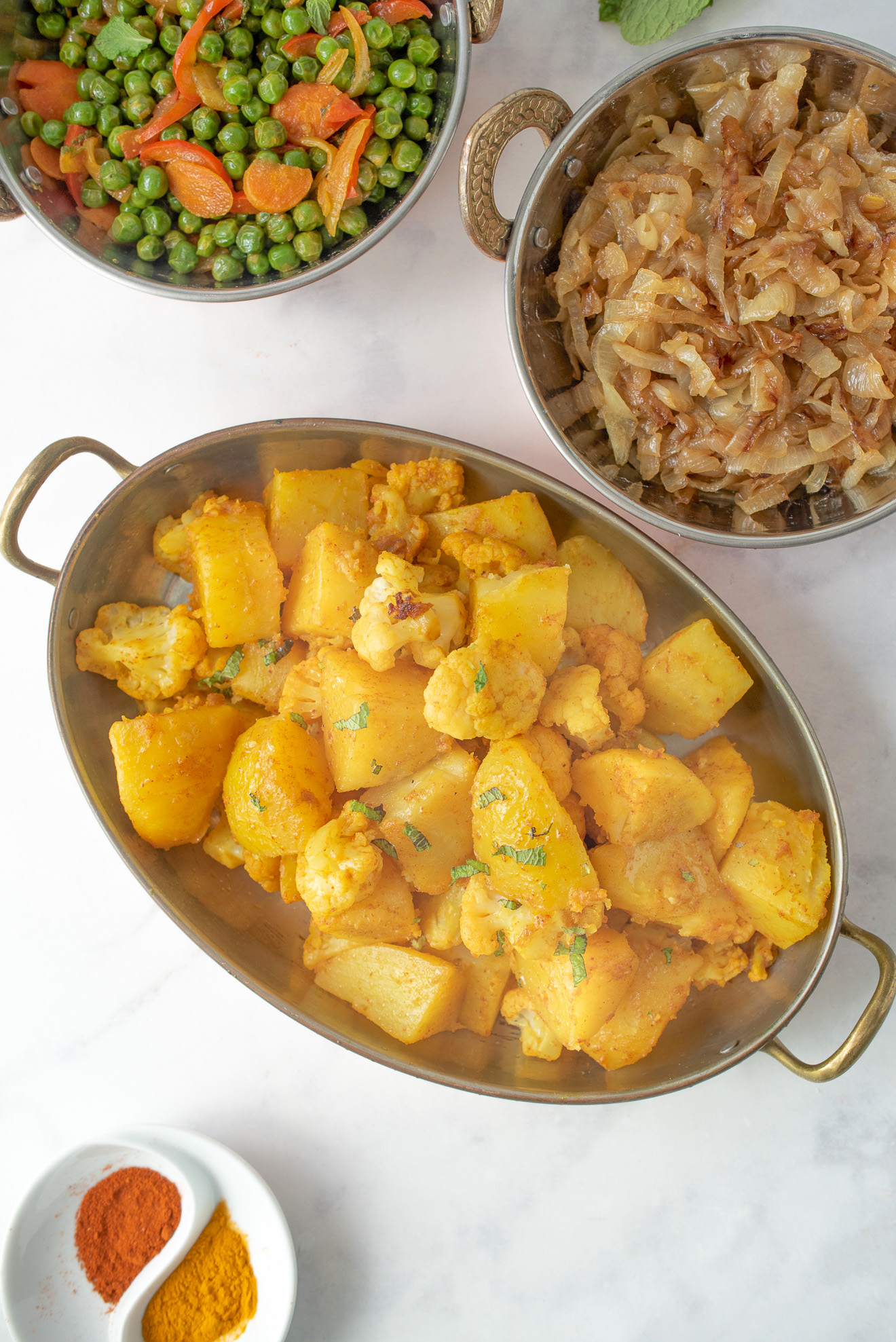 Indian aloo gobi from overhead with peas, curry caramelized onions in serving dishes