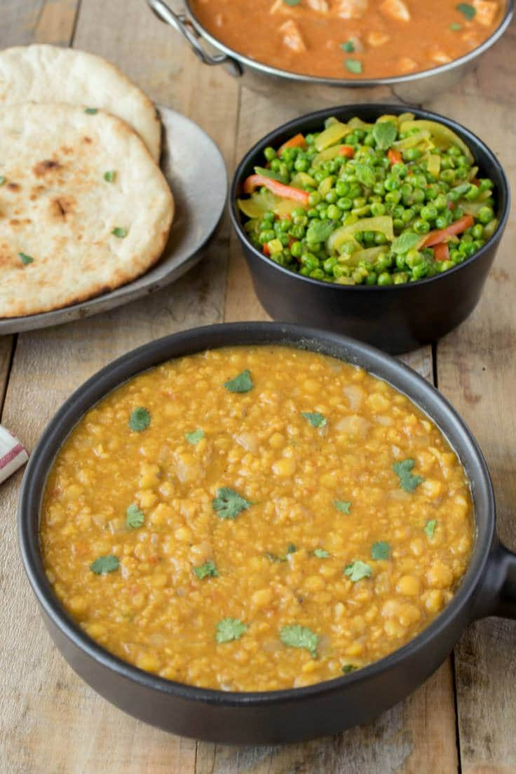 A bowl of Indian dal with naan bread and Indian spiced peas