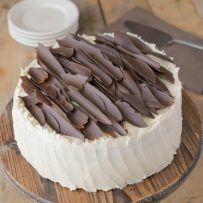 A buttercream frosted chocolate cake topped with chocolate shards on a cake stand