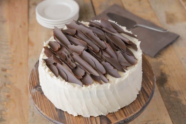 A cream colored frosted cake adorned with chocolate shards on a cake stand
