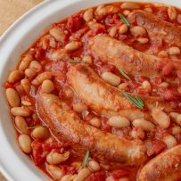 Beans and sausage in a casserole with tomato and rosemary