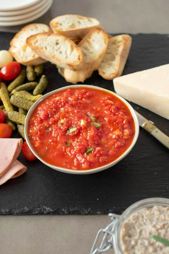 Roasted red pepper relish in a bowl with crusty bread, pickles and cherry tomatoes