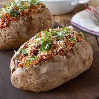 2 Italian sausage microwave baked potatoes on a serving board with forks in the background