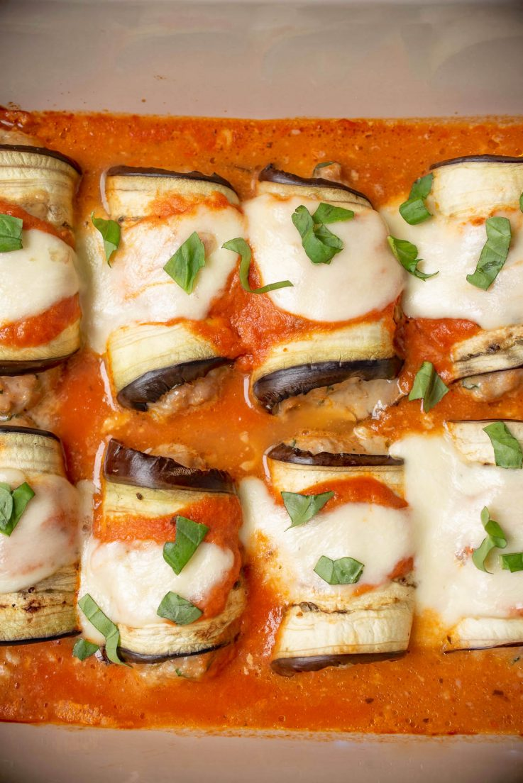 Eggplant rollatini in a baking dish topped with fresh basil