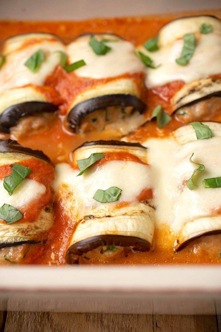 Eggplant rolls lined up in a casserole dish