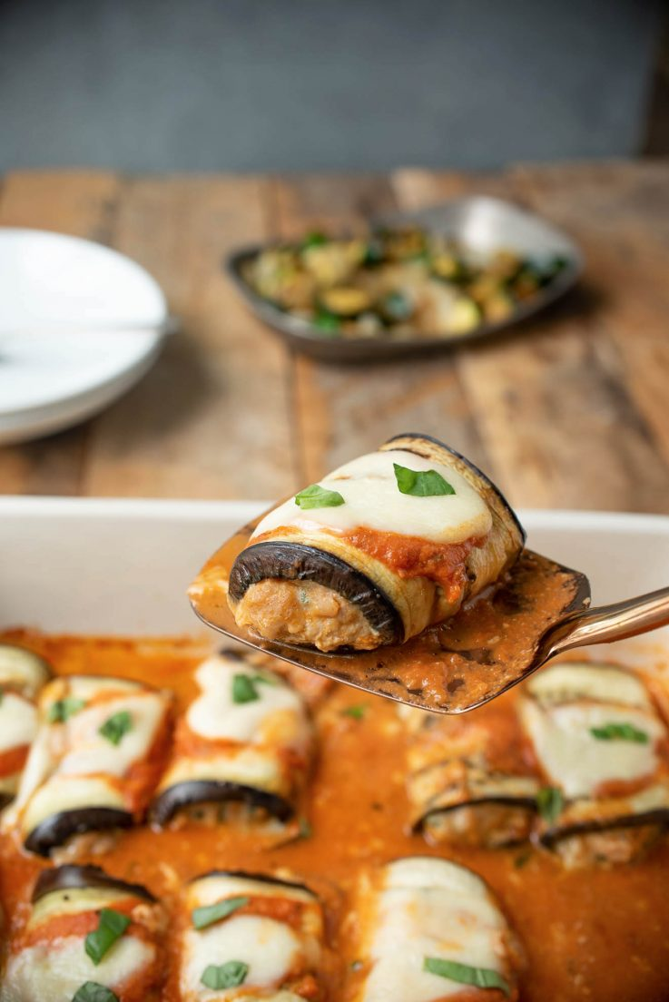 An eggplant roll filled with Italian sausage on a spatula