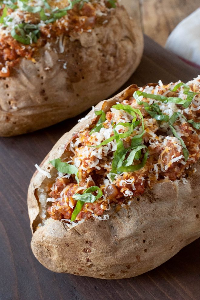 Italian sausage cooked in tomato sauce fills a large russet baked potato