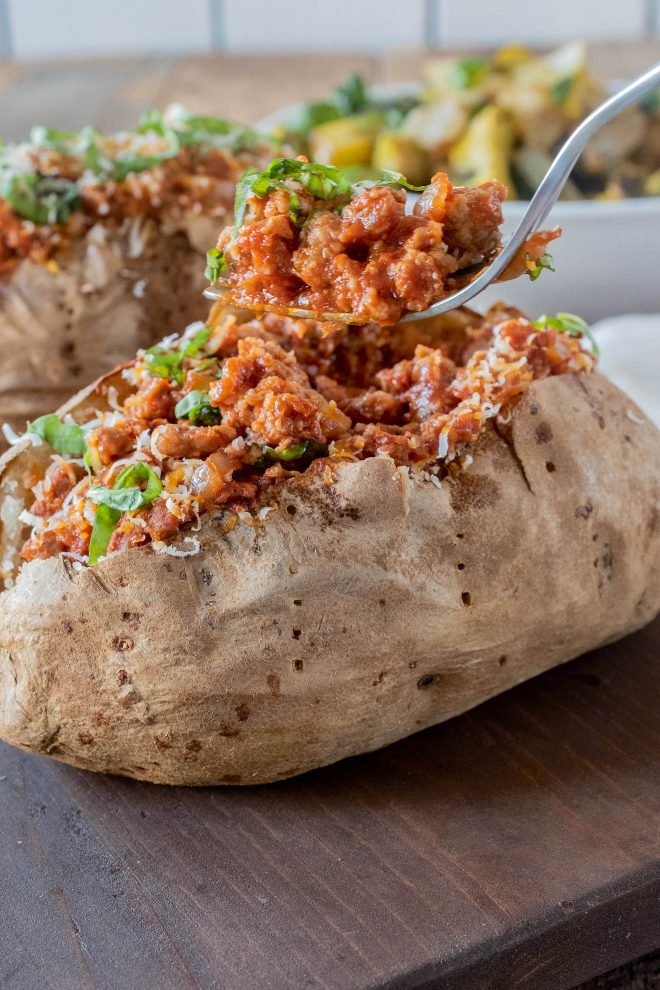 Using a fork to scoop out a bite of the Italian sausage filling from a baked/jacket potato