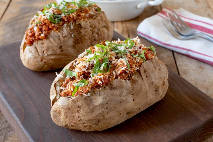 2 baked potatoes filled with Italian sausage and tomato sauce topped with fresh basil