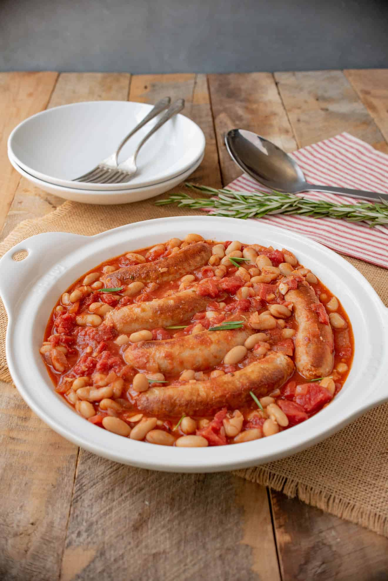 A round white serving bowl with sausage and beans with 2 bowls and forks
