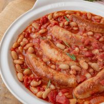 A closeup of the sausages nestled in the beans and tomato sauce