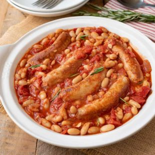 A round serving plate of Italian sausage and beans in a tomato sauce