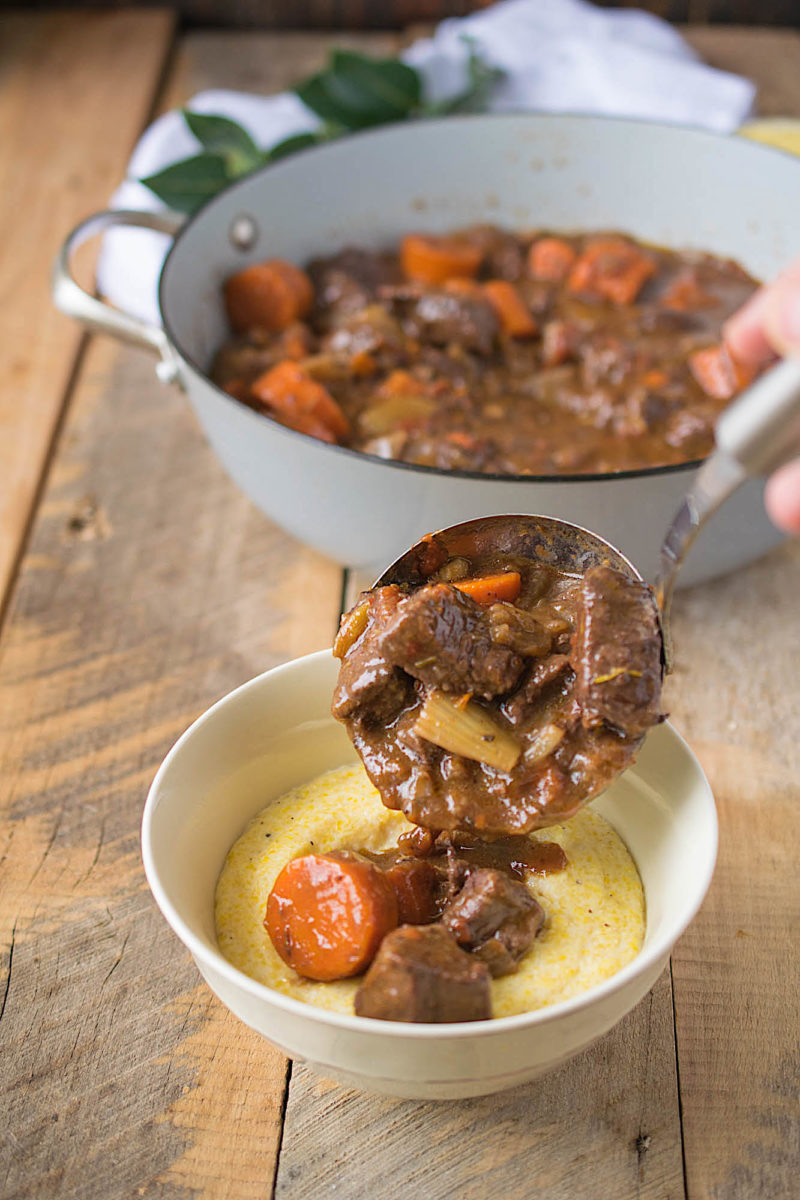 A ladle full of Italian beef stew being poured over polenta into a bowl