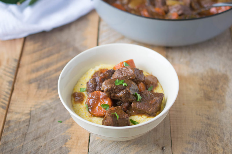 Italian beef stew served in a white bowl over creamy polenta
